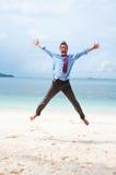 Hombre de negocios divertidos que salta en la playa Fotos de archivo