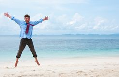 Hombre de negocios divertidos que salta en la playa Foto de archivo libre de regalías