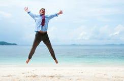 Hombre de negocios divertidos que salta en la playa Imagen de archivo libre de regalías