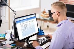 Hombre de negocios Doing Online Banking en oficina imágenes de archivo libres de regalías