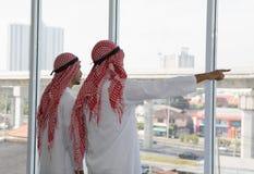 Hombre de negocios de dos árabes que señala al edificio grande del proyecto imagen de archivo libre de regalías
