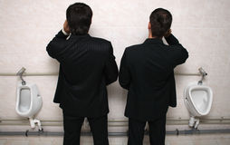 Hombre de negocios dos con los teléfonos móviles en un WC Foto de archivo libre de regalías