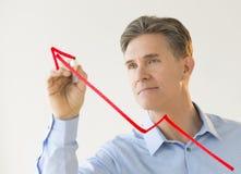 Hombre de negocios Drawing Arrow Moving hacia arriba en tablero transparente Foto de archivo