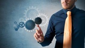 Hombre de negocios e interfaz virtual con las ruedas dentadas Imágenes de archivo libres de regalías