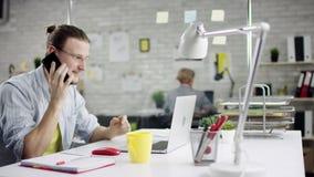 Hombre de negocios eficaz productivo que inclina el trabajo de oficina detrás de acabado en el ordenador portátil, encargado efic almacen de video