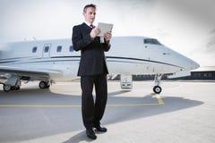 Hombre de negocios ejecutivo delante del jet corporativo que mira el tabl Imagen de archivo libre de regalías