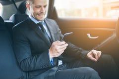 Hombre de negocios ejecutivo en la parte posterior del coche usando un teléfono móvil imagenes de archivo