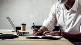 Hombre de negocios elegante adulto que lleva vidrios clásicos y que trabaja con el ordenador portátil en la tabla de madera en de Foto de archivo libre de regalías