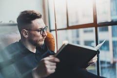Hombre de negocios elegante atractivo que lee el libro negro mientras que se sienta en silla del vintage en su oficina moderna Ho imagenes de archivo