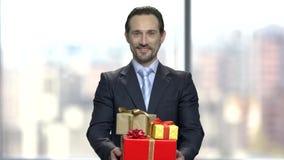 Hombre de negocios elegante con las cajas de regalo almacen de video