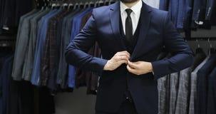 Hombre de negocios elegante en la camisa blanca que corrige su lazo y que abotona su chaqueta del traje Cierre para arriba metrajes