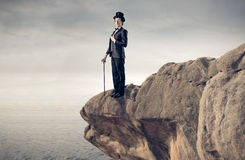 Hombre de negocios elegante en una roca Imagen de archivo libre de regalías