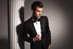 Hombre de negocios elegante joven que fija su chaqueta Foto de archivo libre de regalías