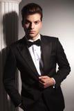 Hombre de negocios elegante joven que fija su chaqueta Imágenes de archivo libres de regalías