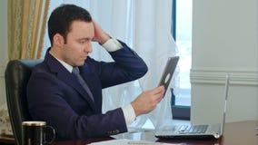 Hombre de negocios elegante que corrige el suyo chaqueta y pelo del traje que miran la tableta moderna almacen de metraje de vídeo