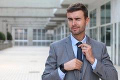 Hombre de negocios elegante que guiña mientras que ajusta su lazo con el espacio de la copia Imagen de archivo