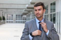 Hombre de negocios elegante que guiña mientras que ajusta su lazo con el espacio de la copia Imagenes de archivo