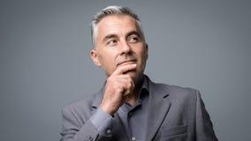 Hombre de negocios elegante que piensa con la mano en la barbilla fotos de archivo libres de regalías