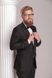 Hombre de negocios elegante que presenta cerca de una columna blanca Fotografía de archivo