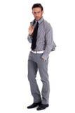 Hombre de negocios elegante que se coloca con su juego Imagenes de archivo