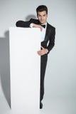 Hombre de negocios elegante que se inclina en un tablero blanco Foto de archivo libre de regalías