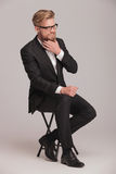 Hombre de negocios elegante que se sienta en un taburete Fotografía de archivo libre de regalías