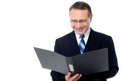 Hombre de negocios elegante que sostiene un fichero abierto Foto de archivo libre de regalías