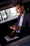 Hombre de negocios elegante que trabaja en automóvil fotografía de archivo