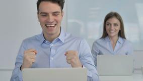 Hombre de negocios emocionado Celebrating Success mientras que trabaja en el ordenador portátil almacen de video