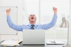 Hombre de negocios emocionado con los brazos para arriba que anima Fotos de archivo