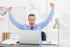 Hombre de negocios emocionado con los brazos para arriba que anima Foto de archivo libre de regalías