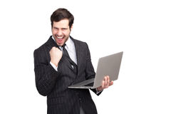 Hombre de negocios emocionado con un ordenador portátil imagenes de archivo