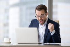 Hombre de negocios emocionado en el ganador de la sensación del traje que celebra la victoria en línea imágenes de archivo libres de regalías