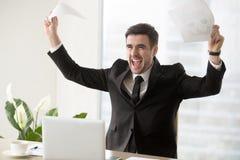 Hombre de negocios emocionado que celebra el éxito empresarial, sosteniendo los papeles imagenes de archivo