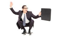 Hombre de negocios emocionado que monta un monopatín para trabajar Imágenes de archivo libres de regalías