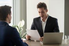 Hombre de negocios emocionado que parece sorprendido mientras que lee el documento, impre Imagen de archivo