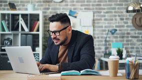 Hombre de negocios emocionado que trabaja con las manos que aplauden de consumición del café del ordenador portátil metrajes
