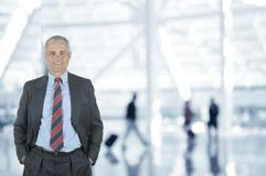 Hombre de negocios en aeropuerto con los viajeros borrosos en fondo Imagen de archivo libre de regalías