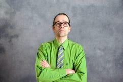 Hombre de negocios en camisa y corbata verdes con los brazos cruzados Fotografía de archivo libre de regalías