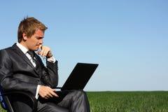 Hombre de negocios en campo, con una computadora portátil. Imagen de archivo libre de regalías