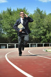 Hombre de negocios en carpeta que lleva del traje y de la corbata en la tensión en pista atlética que habla en el teléfono móvil Fotografía de archivo