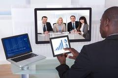 Hombre de negocios en conferencia que analiza el gráfico Foto de archivo
