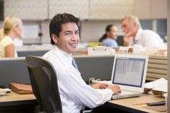 Hombre de negocios en cubículo con la sonrisa de la computadora portátil Imagen de archivo