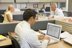 Hombre de negocios en cubículo en la computadora portátil imágenes de archivo libres de regalías