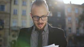 Hombre de negocios en documentos de los ficheros de los vidrios metrajes