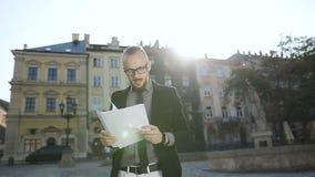 Hombre de negocios en documentos de los ficheros de los vidrios almacen de video