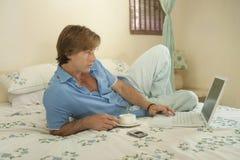 Hombre de negocios en dormitorio con la computadora portátil Imagen de archivo libre de regalías