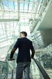 Hombre de negocios en el aeropuerto que va abajo de la escalera móvil Foto de archivo libre de regalías