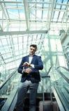 Hombre de negocios en el aeropuerto que va abajo de la escalera móvil Fotografía de archivo libre de regalías