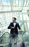Hombre de negocios en el aeropuerto que va abajo de la escalera móvil Fotos de archivo libres de regalías